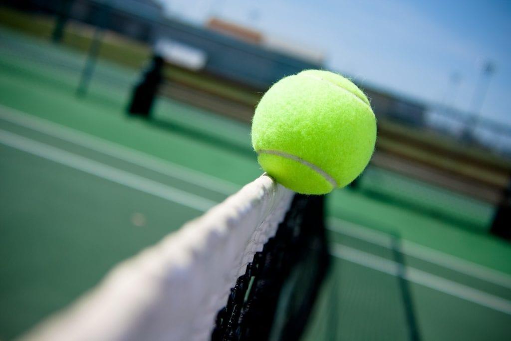 tennis ball balancing on net
