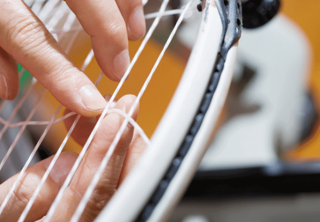 threading crosses while stringing tennis racket